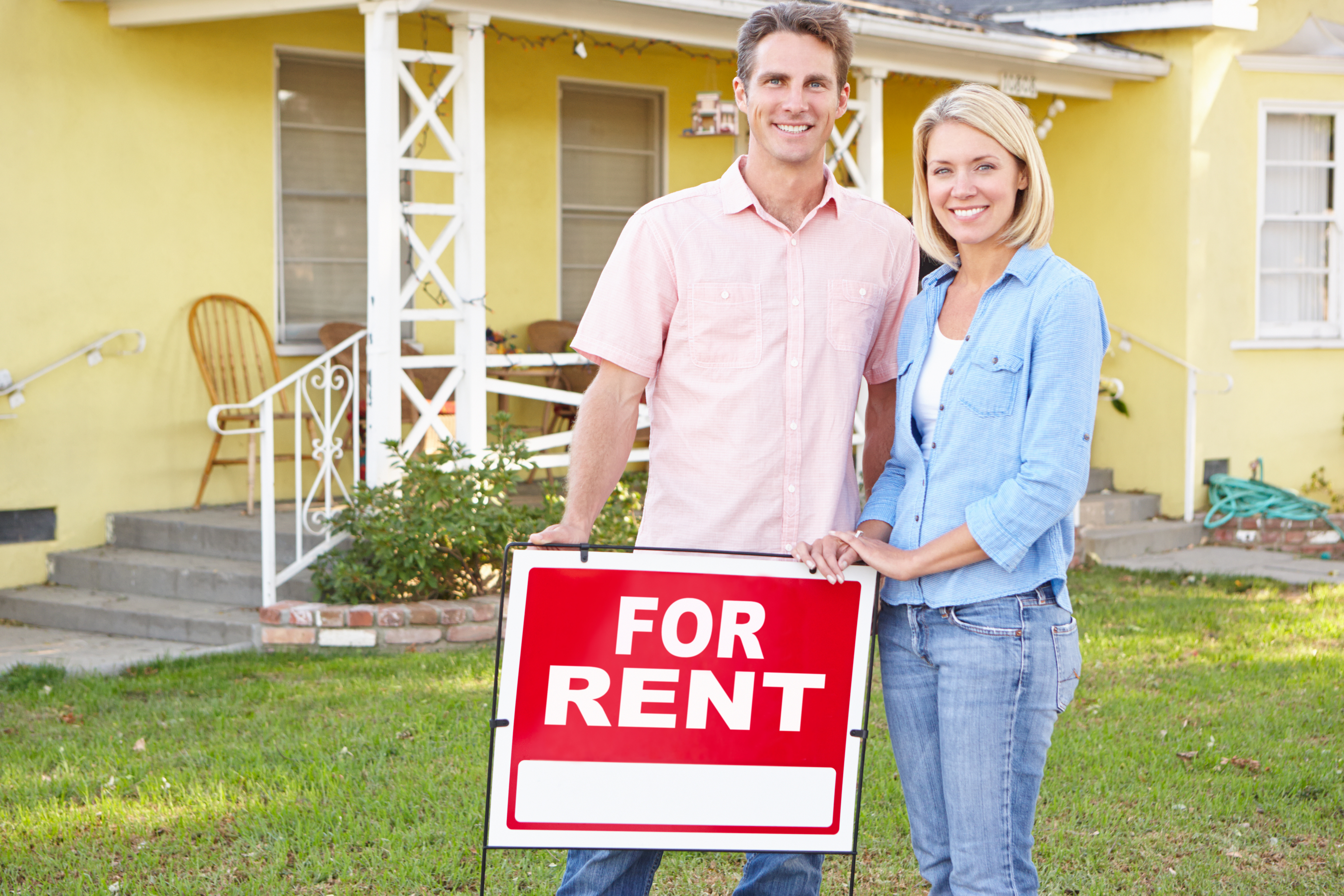 Lovely Couple Standing By For Rent Sign Outside Home